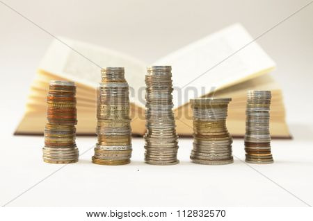Stakes of diverse coins foreground open book background on white