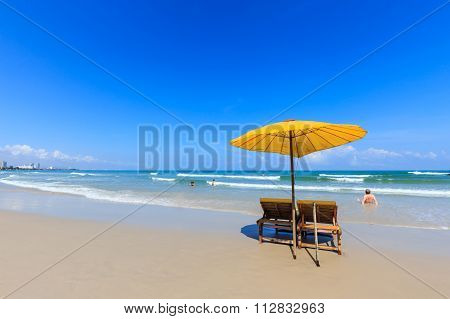 Yellow Umbrella And Wooden Chairs On The Beach