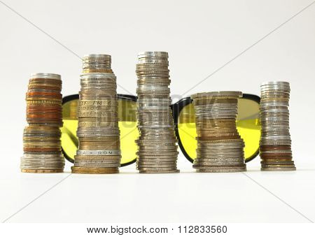 Sunglasses background stakes of diverse coins foreground on white