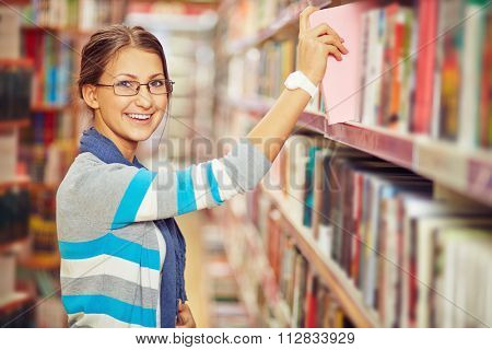 Teenage girl looking for a book in library