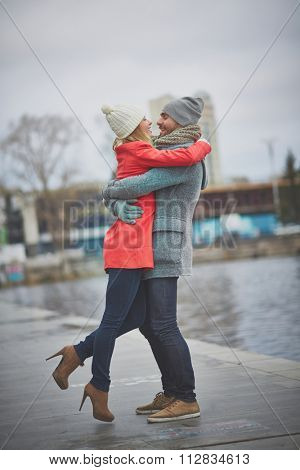 Happy amorous couple embracing in urban environment