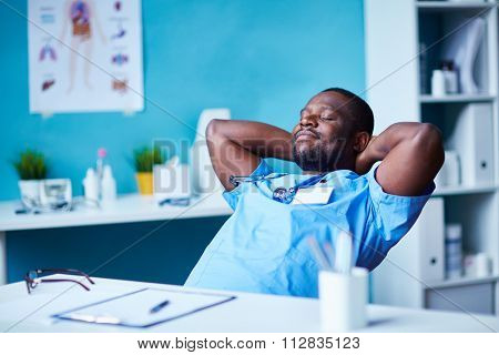 Young clinician with closed eyes relaxing at workplace
