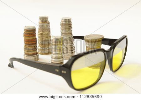 Sunglasses foreground stakes of diverse coins background on white