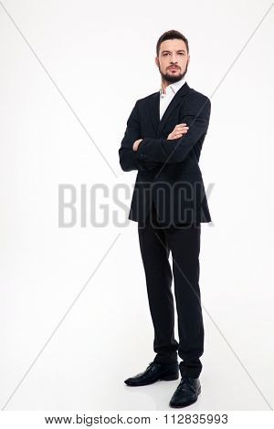 Full length portrait of a serious businessman standing with arms folded isolated on a white background