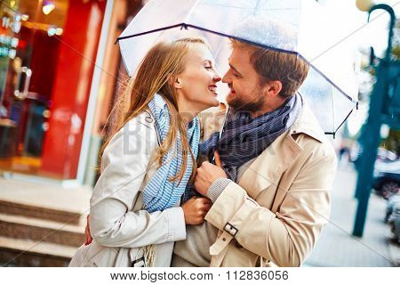 Amorous young couple laughing under umbrella