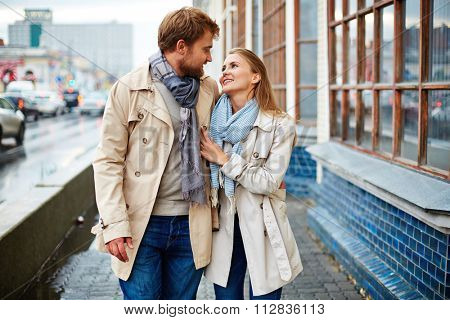 Amorous couple taking walk in urban environment