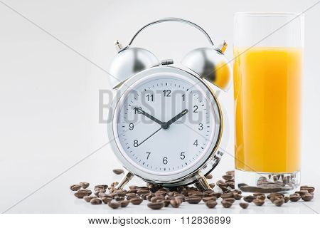 Alarm clock and fresh juice on the surface