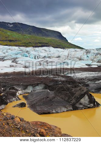 Skaftafell National Park. The southern part of the huge Vatnajokull glacier. Blue ice covered ground black volcanic ash