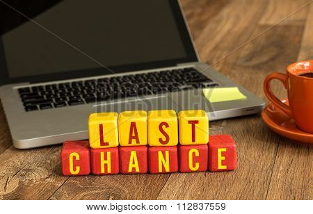 Last Chance written on a wooden cube in a office desk