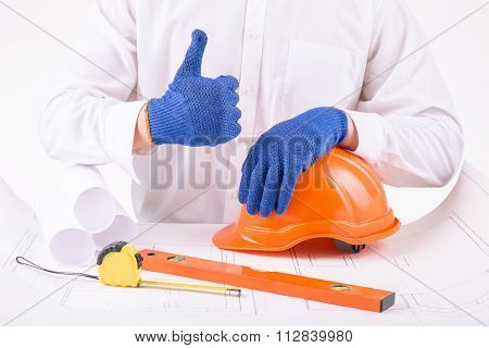 Person in protective gloves showing thumbs up.