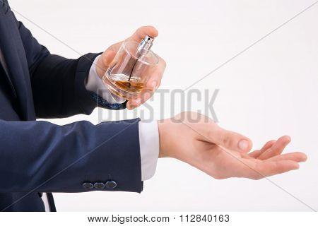 Man spraying perfume on his wrist.