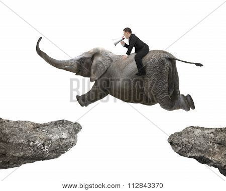Man With Using Speaker Riding Elephant Flying Over Two Cliffs