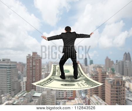 Rear View Businessman Balancing On Money Flying Carpet