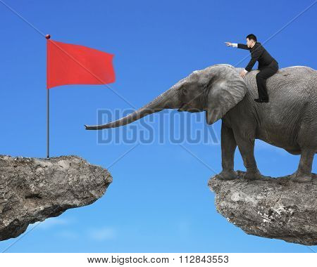 Man With Pointing Finger Riding Elephant Toward Red Flag