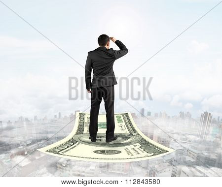 Businessman Standing On Money Flying Carpet Watching The Front