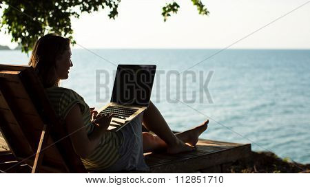 Silhouette of woman with laptop sitting in a deckchair at the seaside.