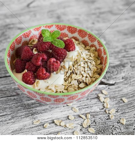 Oatmeal With Raspberries, Strawberries And Natural Yoghurt In A Bowl On A Light Wooden Background