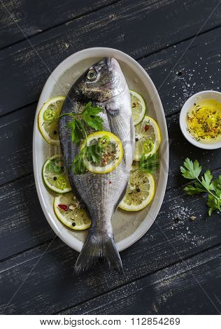 Fresh Dorado Fish With Lemon, Lime And Parsley On An Oval Dish On Dark Wooden Background