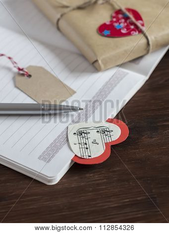 Notebook,  Homemade Bookmark And A Handmade Valentine's Day Gift In Kraft Paper On Wooden Table