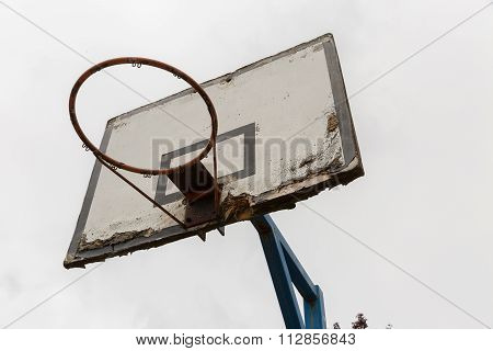 An Old Basketball Ring With A White Wooden Plate Where Paint Is Peeling Off And Fixed To A Blue Stee
