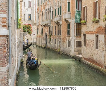 Venetian gondolier punting gondola through green canal waters