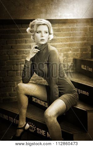 Young beautiful short hair blonde woman in turtle neck tight short dress sitting on stairs