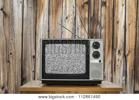 Vintage television with rustic wood wall and static screen.