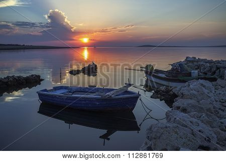 boats at sunset, tethered to the shore