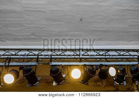Bright Spotlights  Hanging From The Wall. Big Gray Wall With Many Spotlights  On A Rail Which Glows