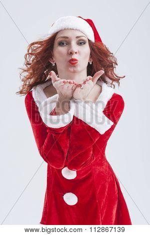 Happy Flirting Caucasian Female Santa Helper Sending Air Kiss