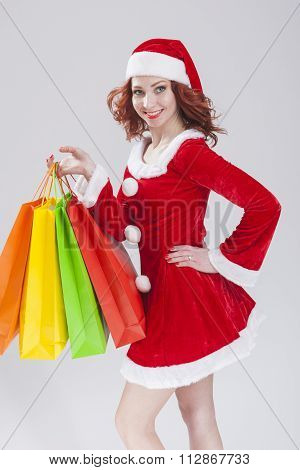 Smiling Red Haired Female Santa Helper with Shopping Bags