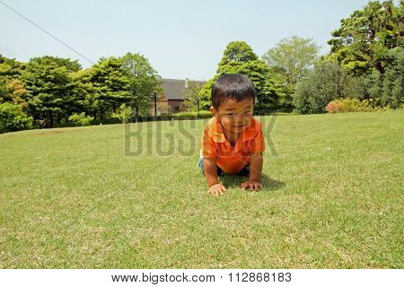 Japanese boy crawling on the grass (1 year old)