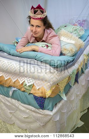 One woman is laying like mollycoddle on the many mattresses under a bed curtain.