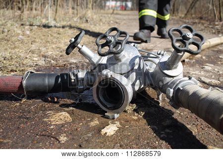Faucet from firefighter hose on the ground in a park.