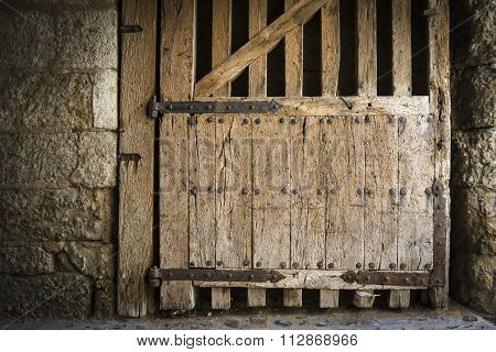 ancient wooden gate with rusty metal hinges