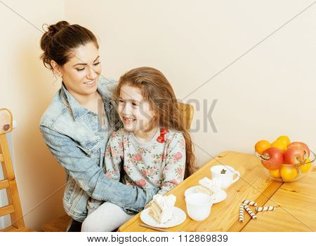 young mother with daughter on kitchen drinking tea together hugging eating celebration cake smiling,