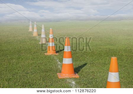 Traffic road cone pylon on green grass