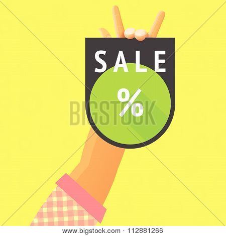 sale percent sign inscription placard hold by hand's fingers at checkered t-shirt