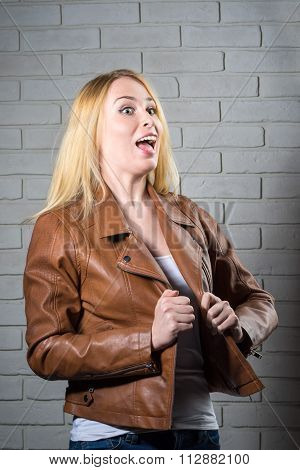 Portrait Of A Roaring Young Woman Looking Up With Her Mouth Open On A Brick Wall Background