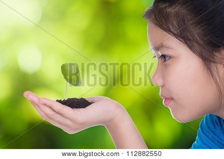 A Girl Holding A Seedling In Hand. She Is Going To Grow. Agriculture  Concept With Green Background.