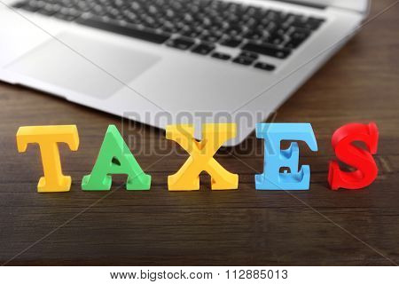 Alphabet TAXES and laptop on wooden table