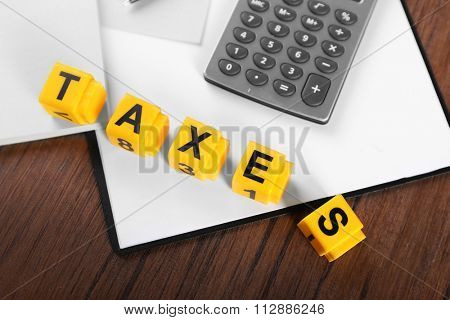 Alphabet TAXES and calculator with papers on wooden table