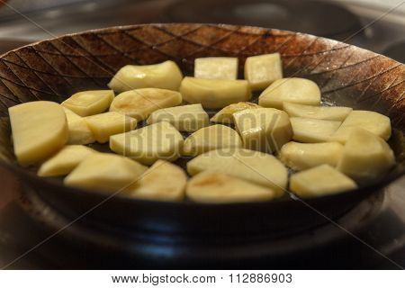 Raw chip potatoes in iron frying pan