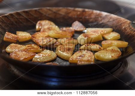 Crispy brown chip potatoes in iron frying pan