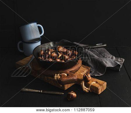 Roasted chestnuts in skillet cooking pan over rusti wooden boards, blue enamel mugs, towel on dark b