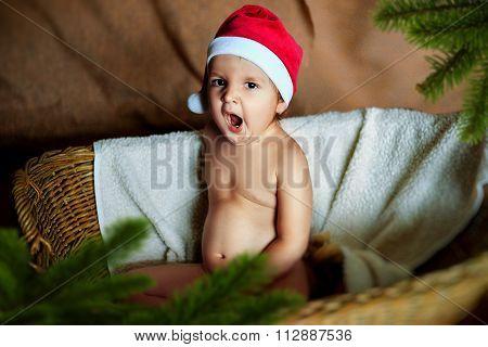 Little Baby Boy in Santa hat sitting in a wicker basket.