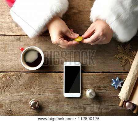 Christmas concept. Santa takes candy in hands. Smart phone, cup of coffee, wish list and decorations on wooden table, close up