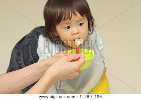 Japanese baby girl eating baby food (1 year old)