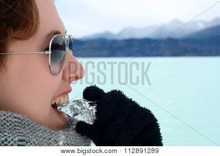 Young Woman Biting Ice At A Glacier. Happy  Woman In The Patagonia Argentina.