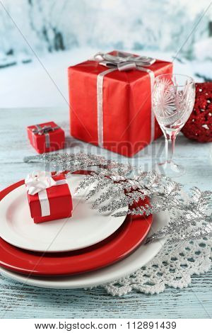 Table appointments with present boxes on color wooden table and light background